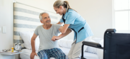 Healthcare worker helping elderly man out of bed.