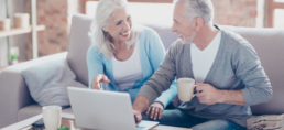 Elderly woman and man sitting on couch with computer.